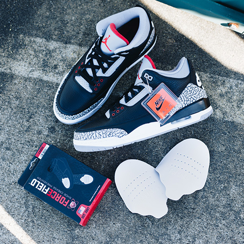 Pair of Air Jordan 3 Black Cements laying on sidewalk next to box of ForceField Crease Preventers and Crease Preventers out of the box